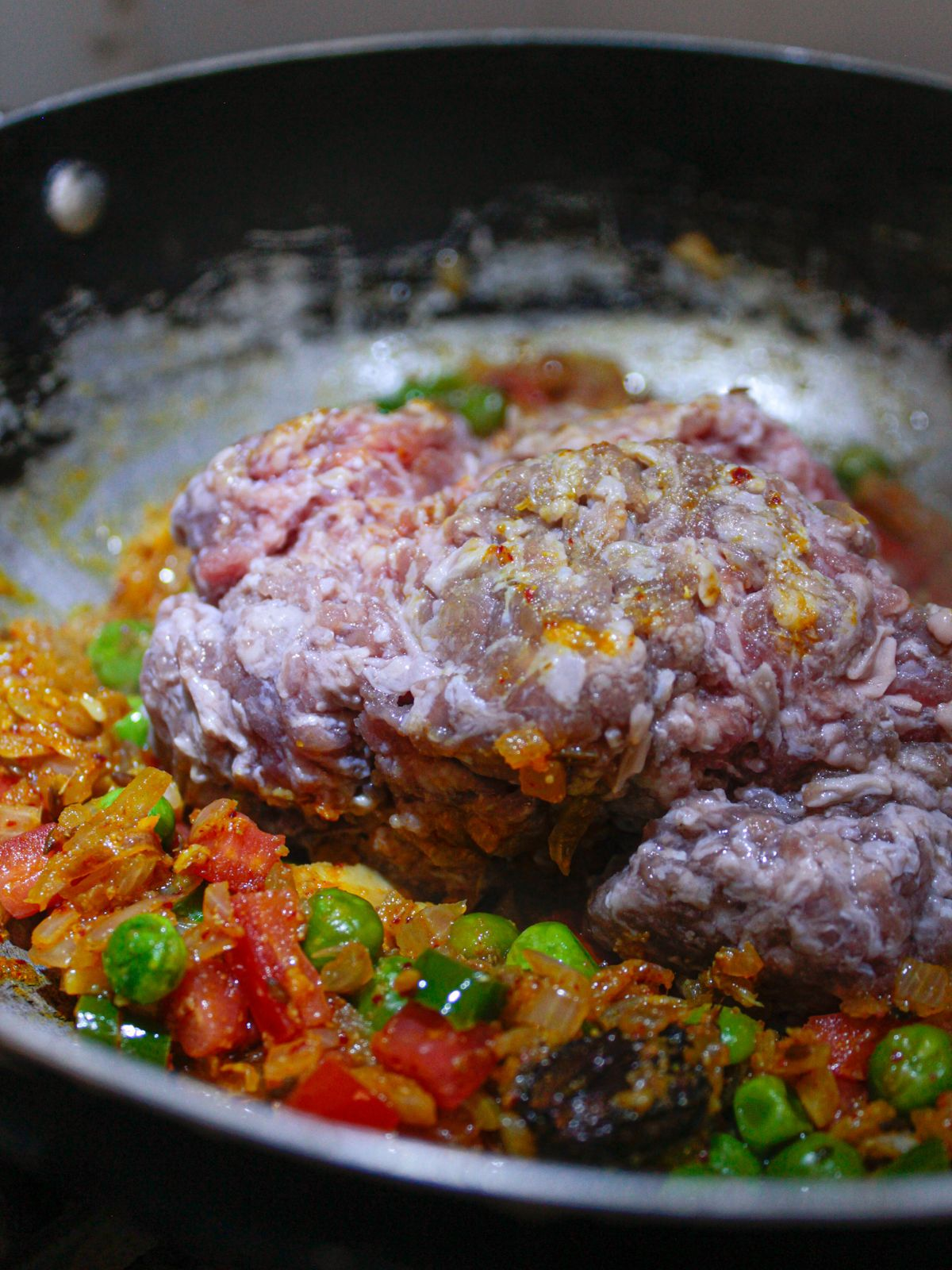 Raw ground mutton on top of peas and tomatoes in skillet