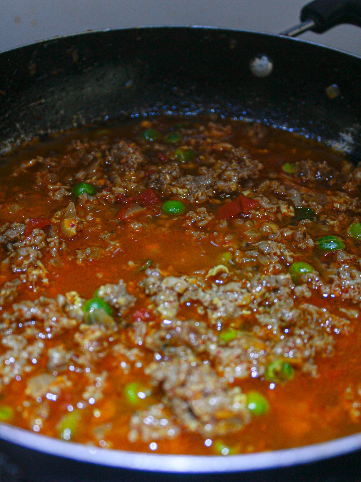 Mutton curry simmering in sauce in skillet