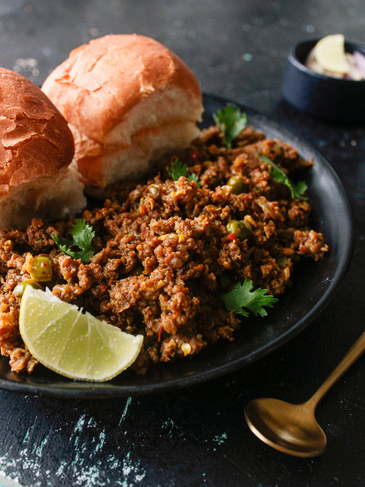 Black plate of keema with pav and lime on black table by gold spoon