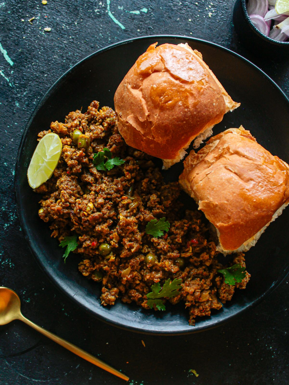 Black plate of keema with lemon wedge and two rolls on top