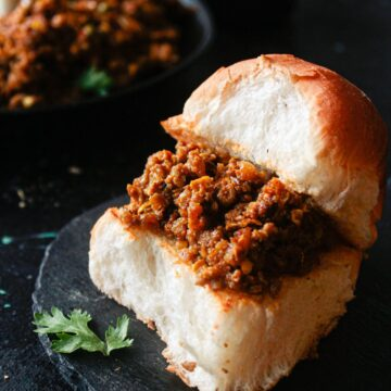 Bun filled with mutton curry on black plate