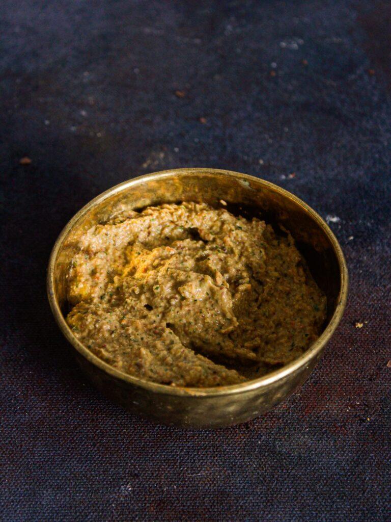 gold bowl of peanut chutney on black table