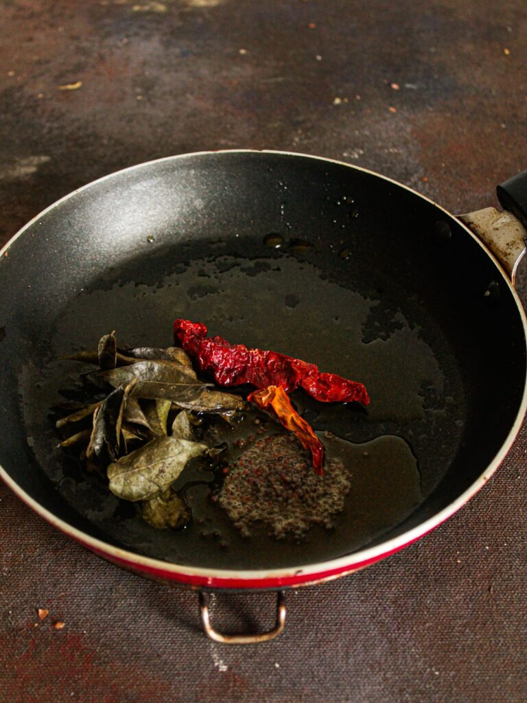 Curry leaves red chiles and seeds in oil in skillet