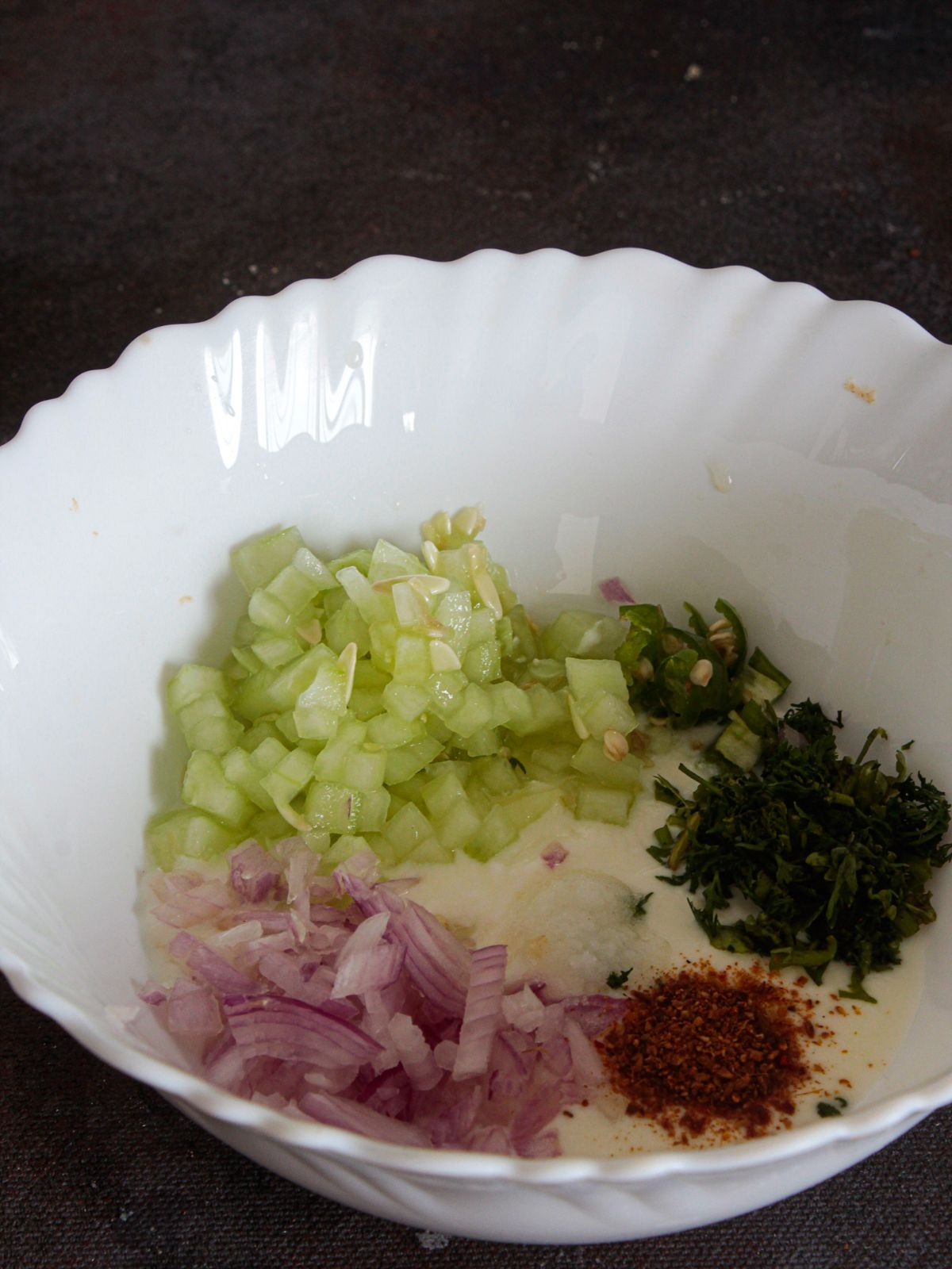 White bowl filled with yogurt cucumbers onions and herbs