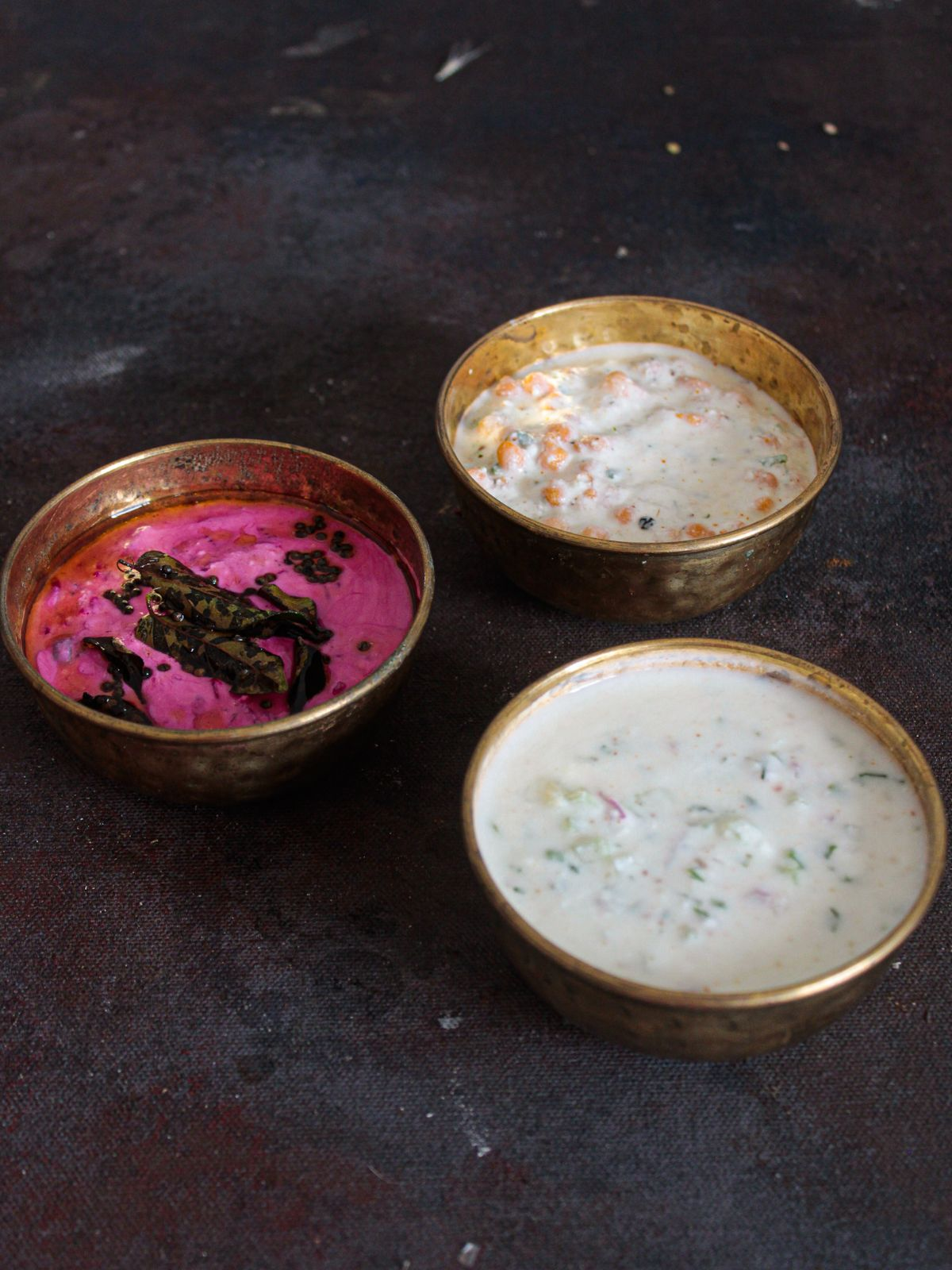 Three gold bowls filled with raita in white and pink