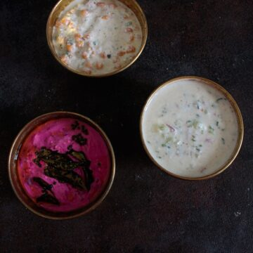 Three gold bowls of raita on black table