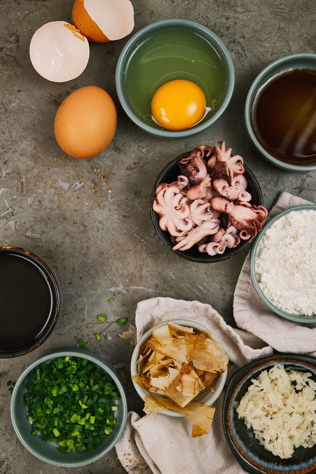 Octopus, eggs, and flour in bowls on gray table