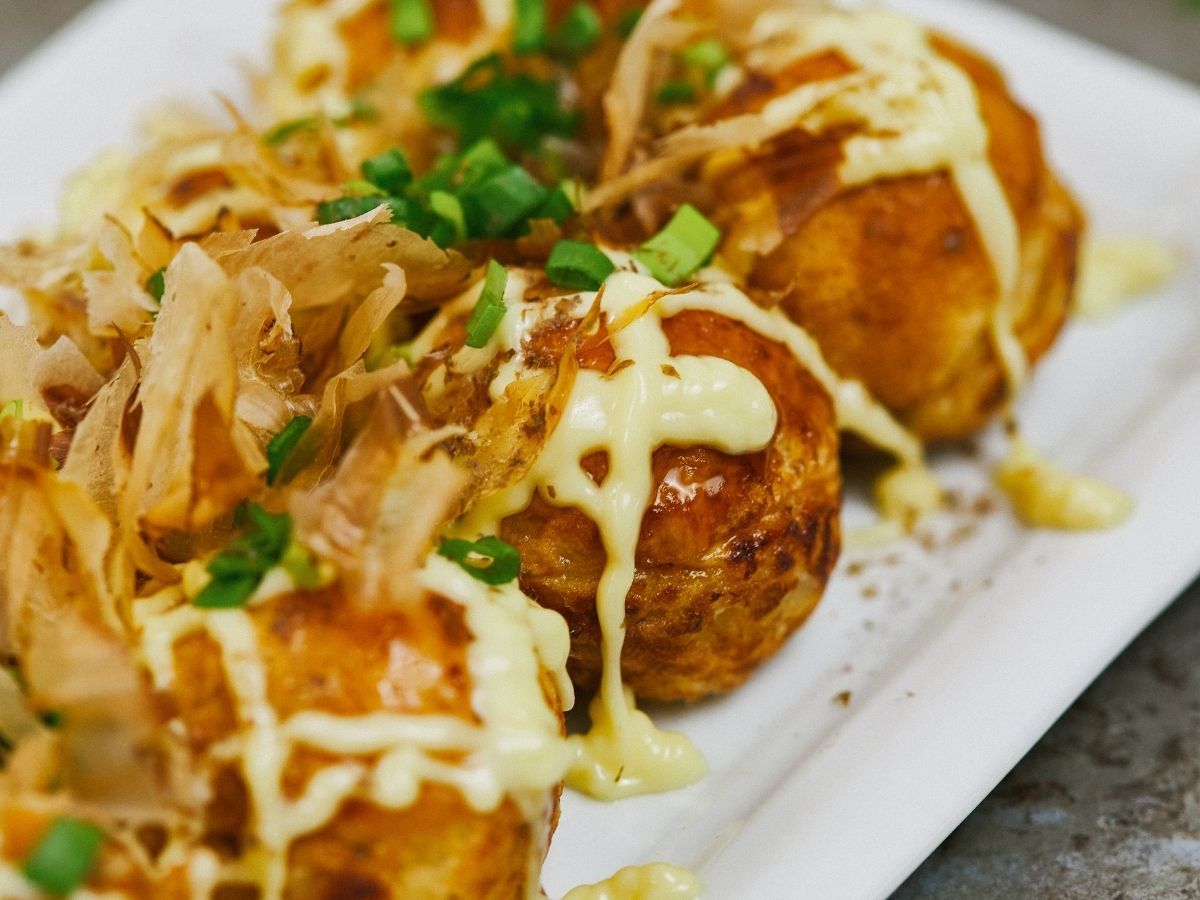Takoyaki balls on white platter with traditional toppings