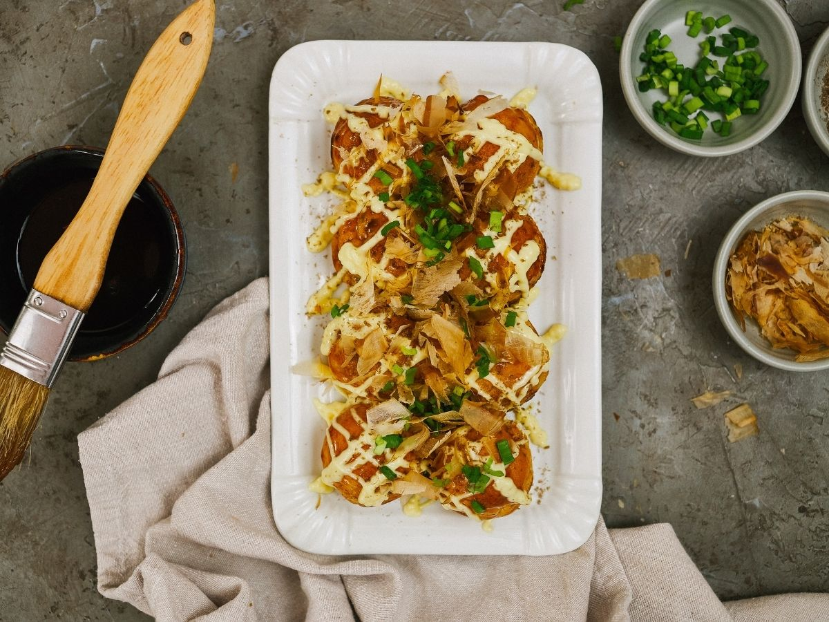 white platter of takoyaki on gray table by bowl of green onions and pink napkin