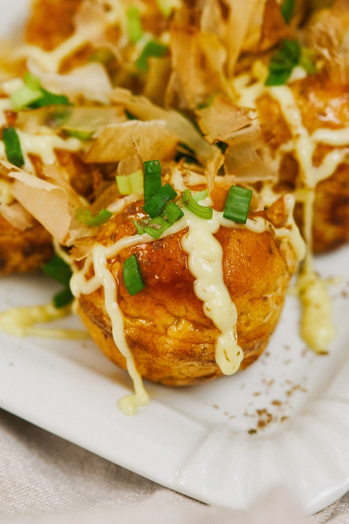 octopus ball with mayonnaise and green onions sitting on plate